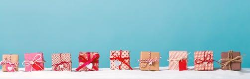 Κιβώτια δώρων Χριστουγέννων σε ένα χιονισμένο τοπίο Στοκ Εικόνες