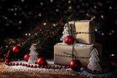 Κιβώτια δώρων Χριστουγέννων στο έγγραφο του Κραφτ που διακοσμείται με τα κόκκινα μπιχλιμπίδια, Στοκ εικόνα με δικαίωμα ελεύθερης χρήσης