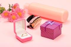 Κιβώτια και καλλυντικά δώρων σε ένα ρόδινο υπόβαθρο με τα λουλούδια στοκ εικόνα με δικαίωμα ελεύθερης χρήσης