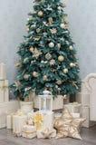 Κιβώτια των δώρων με μια χρυσή κορδέλλα κάτω από ένα διακοσμημένο δέντρο Στοκ εικόνα με δικαίωμα ελεύθερης χρήσης