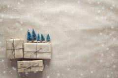 Κιβώτια δώρων με τα μικροσκοπικά διακοσμητικά δέντρα έλατου στο καφετί τύλιγμα Στοκ Εικόνα
