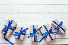 Κιβώτια δώρων με τις μπλε κορδέλλες στο άσπρο χρωματισμένο ξύλινο υπόβαθρο Στοκ Φωτογραφία