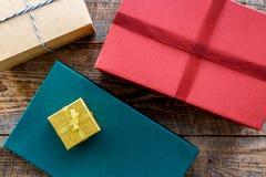 Κιβώτια δώρων που τυλίγονται στο χρωματισμένο έγγραφο που σχετίζεται με την κορδέλλα στην ξύλινη τοπ άποψη υποβάθρου Στοκ Εικόνα