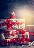 Κιβώτια δώρων Χριστουγέννων με το έγγραφο και κόκκινες κορδέλλες στο γκρίζο αγροτικό υπόβαθρο Στοκ Εικόνες