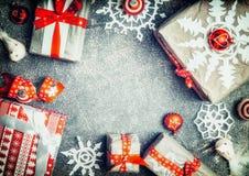 Κιβώτια δώρων Χριστουγέννων με snowflakes εγγράφου, τις κόκκινες κορδέλλες και τις εορταστικές διακοσμήσεις, τοπ άποψη Στοκ Εικόνα