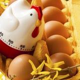 Κιβώτιο αυγών χαρτονιού με τα αυγά και το χρονόμετρο Στοκ εικόνες με δικαίωμα ελεύθερης χρήσης