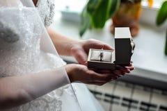 Κιβώτιο δαχτυλιδιών αρραβώνων στα χέρια νυφών Κινηματογράφηση σε πρώτο πλάνο των φοινικών γυναικών που κρατούν τα κοσμήματα Στοκ φωτογραφία με δικαίωμα ελεύθερης χρήσης
