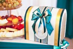 Κιβώτιο για τα χρήματα στο γαμήλιους πίνακα και τα φρούτα Στοκ Εικόνα