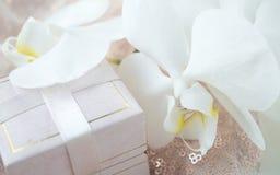 Κιβώτιο δώρων για τις διακοσμήσεις με ένα λουλούδι ορχιδεών ενάντια σε ένα λαμπρό φ Στοκ φωτογραφίες με δικαίωμα ελεύθερης χρήσης