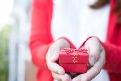 Κιβώτιο δώρων εκμετάλλευσης γυναικών ασιατικό θηλυκό άσπρο πουκάμισο ένδυσης και κόκκινο kn Στοκ Φωτογραφία