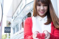 Κιβώτιο δώρων εκμετάλλευσης γυναικών ασιατικό θηλυκό άσπρο πουκάμισο ένδυσης και κόκκινο kn Στοκ Εικόνες
