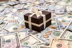 Κιβώτιο δώρων επάνω από τους λογαριασμούς δολαρίων ως υπόβαθρο στοκ εικόνα με δικαίωμα ελεύθερης χρήσης