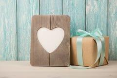 Κιβώτιο δώρων και διαμορφωμένο καρδιά πλαίσιο στον ξύλινο πίνακα Στοκ εικόνα με δικαίωμα ελεύθερης χρήσης