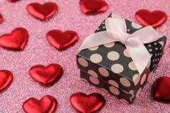 Κιβώτιο δώρων και κόκκινη κινηματογράφηση σε πρώτο πλάνο καρδιών σε ένα φωτεινό λαμπρό ρόδινο υπόβαθρο βαλεντίνος ημέρας s στοκ εικόνες