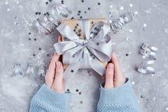 Κιβώτιο δώρων λαβής χεριών γυναικών που τυλίγεται στο έγγραφο του Κραφτ στοκ φωτογραφία με δικαίωμα ελεύθερης χρήσης