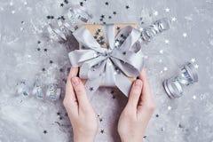 Κιβώτιο δώρων λαβής χεριών γυναικών που τυλίγεται στο έγγραφο του Κραφτ στοκ εικόνα με δικαίωμα ελεύθερης χρήσης