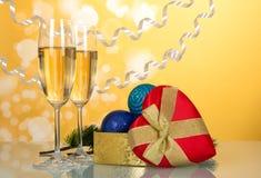 Κιβώτιο δώρων με μορφή της καρδιάς, των διακοσμήσεων Χριστουγέννων και των γυαλιών με το κρασί, στο κίτρινο υπόβαθρο Στοκ εικόνα με δικαίωμα ελεύθερης χρήσης