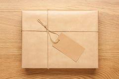Κιβώτιο δώρων που τυλίγεται στο έγγραφο του Κραφτ για τον ξύλινο πίνακα στοκ φωτογραφία