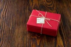Κιβώτιο δώρων στο κόκκινο έγγραφο για το παλαιό ξύλινο υπόβαθρο Στοκ Φωτογραφίες