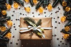 Κιβώτιο δώρων Χριστουγέννων με ένα τόξο και μια όμορφη καμμένος γιρλάντα στο άσπρο ξύλινο κλίμα με τους κλάδους στοκ εικόνες