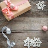Κιβώτιο δώρων Χριστουγέννων με τη ρόδινες κορδέλλα και τη σφαίρα, ντεκόρ από snowflakes, ασημένια κορδέλλα και ντεκόρ γύρω Στοκ Εικόνες