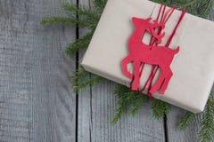 Κιβώτιο δώρων Χριστουγέννων στον αγροτικό πίνακα, τάρανδος ντεκόρ, τύλιγμα βιοτεχνίας, περγαμηνή, κλαδίσκοι δέντρων έλατου Τοπ όψ Στοκ Φωτογραφία