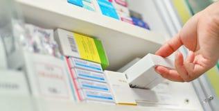 κιβώτιο ιατρικής εκμετάλλευσης χεριών φαρμακοποιών στο φαρμακείο στοκ εικόνες