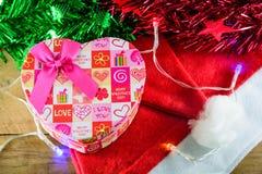 Κιβώτιο και διακοσμήσεις δώρων καρδιών Χριστουγέννων σε ξύλινο Στοκ Φωτογραφίες