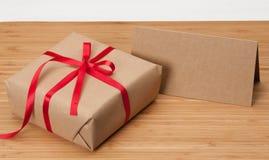 Κιβώτιο και κάρτα δώρων στο ξύλινο υπόβαθρο Στοκ Φωτογραφία