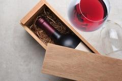 Κιβώτιο κρασιού Cabernet: Ένα ενιαίο μπουκάλι του κόκκινου κρασιού σε μια ξύλινη ισοτιμία κιβωτίων στοκ εικόνες