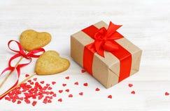 Κιβώτιο με ένα δώρο που τυλίγεται στο έγγραφο του Κραφτ και που δένεται με ένα κόκκινο ribbo Στοκ Εικόνες