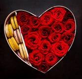 Κιβώτιο με μορφή μιας καρδιάς με τα κόκκινα τριαντάφυλλα και macaroon βαλεντίνος δώρων s ημέρας Στοκ Εικόνες
