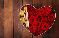 Κιβώτιο με μορφή μιας καρδιάς με τα κόκκινα τριαντάφυλλα και macaroon βαλεντίνος δώρων s ημέρας Στοκ Φωτογραφία