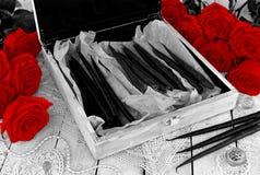 Κιβώτιο με τα μαύρα κεριά, τις διακοσμήσεις και τα κόκκινα τριαντάφυλλα στον πίνακα μαγισσών Στοκ Εικόνες