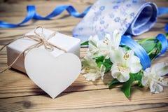 Κιβώτιο, λουλούδια, κάρτα, κορδέλλα και δεσμός δώρων στον ξύλινο πίνακα Στοκ Εικόνες