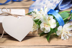Κιβώτιο, λουλούδια, κάρτα, κορδέλλα και δεσμός δώρων στον ξύλινο πίνακα Στοκ φωτογραφίες με δικαίωμα ελεύθερης χρήσης