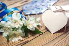Κιβώτιο, λουλούδια, κάρτα, κορδέλλα και δεσμός δώρων στον ξύλινο πίνακα Στοκ φωτογραφία με δικαίωμα ελεύθερης χρήσης