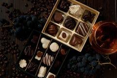 Κιβώτιο σοκολάτας των πραλινών, γλυκό κιβώτιο δώρων, κρασί για ένα ρομαντικό λ Στοκ Φωτογραφίες