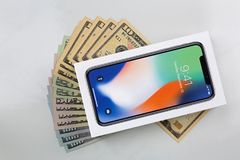 Κιβώτιο του νέου iPhone Χ iPhone 10 στα αμερικανικά χρήματα τραπεζογραμματίων στο μΑ Στοκ εικόνες με δικαίωμα ελεύθερης χρήσης
