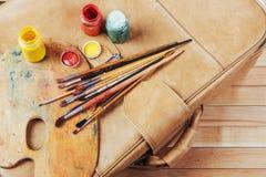 Κιβώτιο των χρωμάτων watercolor, βούρτσες τέχνης στον καμβά Στοκ Φωτογραφίες