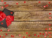Κιβώτιο δώρων με την κόκκινη κορδέλλα τόξων και καρδιά εγγράφου στον ξύλινο πίνακα για την ημέρα βαλεντίνων στοκ φωτογραφία