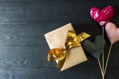 Κιβώτιο δώρων με τη χρυσή κορδέλλα και τις χειροποίητες καρδιές Στοκ Φωτογραφία