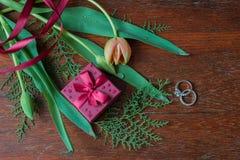 Κιβώτιο δώρων με τις τουλίπες και τα χορτάρια και δαχτυλίδια αρραβώνων στο ξύλο wa Στοκ Φωτογραφία