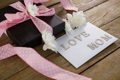 Κιβώτιο δώρων με το κείμενο αγάπης mom στην ξύλινη σανίδα Στοκ φωτογραφίες με δικαίωμα ελεύθερης χρήσης