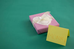 Κιβώτιο δώρων με το κείμενο mom στην κάρτα στο πράσινο κλίμα Στοκ Φωτογραφία