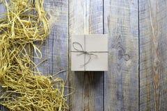 Κιβώτιο δώρων τεχνών στον ξύλινο πίνακα με raffia ή το σπάγγο Στοκ φωτογραφία με δικαίωμα ελεύθερης χρήσης