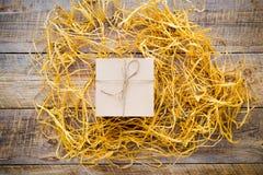 Κιβώτιο δώρων της Kraft στον ξύλινο πίνακα με raffia ή το σπάγγο Στοκ εικόνες με δικαίωμα ελεύθερης χρήσης