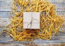 Κιβώτιο δώρων της Kraft στον ξύλινο πίνακα με raffia ή το σπάγγο Στοκ Φωτογραφία