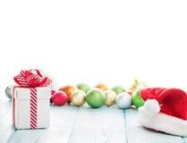 Κιβώτιο δώρων Χριστουγέννων, καπέλο santa και ζωηρόχρωμα μπιχλιμπίδια Στοκ φωτογραφία με δικαίωμα ελεύθερης χρήσης