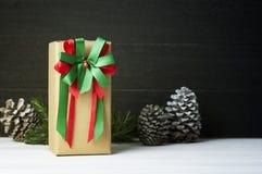Κιβώτιο δώρων Χριστουγέννων στο λευκό ξύλινο πίνακα με τους κώνους πεύκων Στοκ Φωτογραφίες